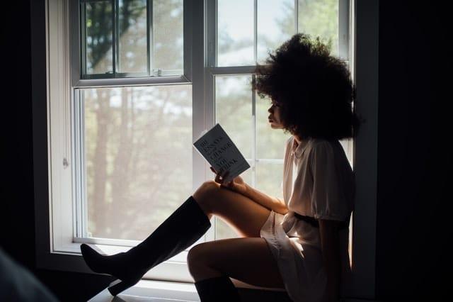 Eine Frau sitzt an einem Fenster und liest ein Buch