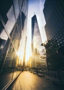 Die Sonne strahlt zwischen zwei verglasten Wolkenkratzern hindurch