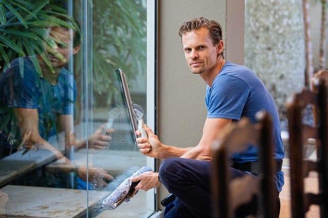 Ein Mann putzt große Fenster