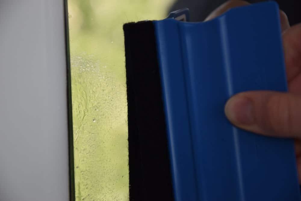 Jemand reinigt mit einem Rakel die Kanten einer Fensterfolie