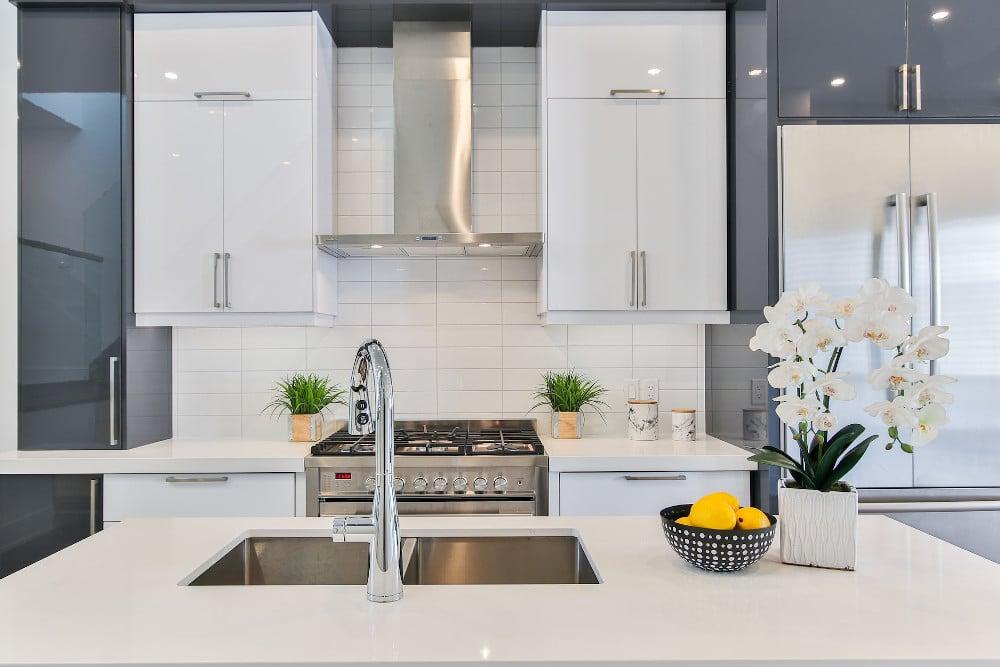 Eine Küchenzeile mit weiß und grau glänzenden Fronten