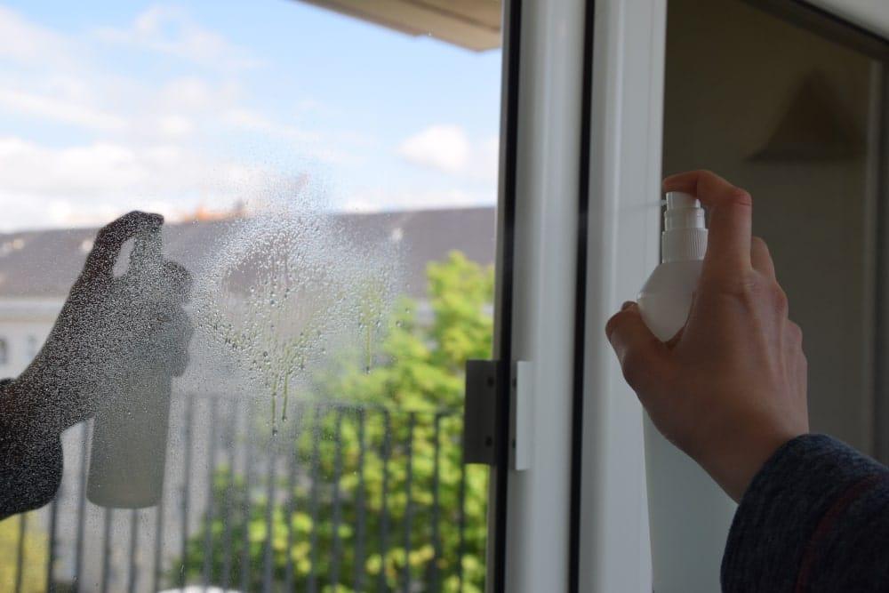 Jemand sprüht eine Fensterfolie mit Glasreiniger ein