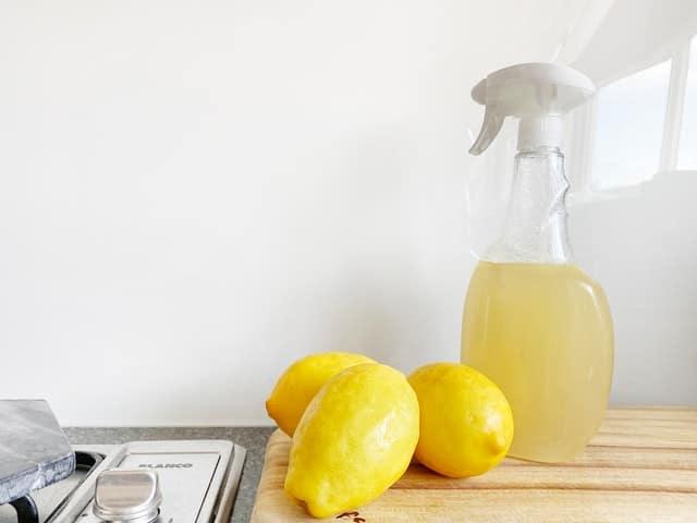 Eine Sprühflasche steht auf einer Arbeitsplatte und daneben liegen zwei Zitronen