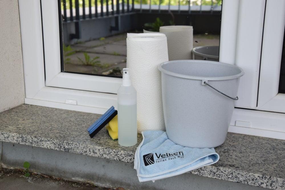 Vor einem Fenster mit einer Spiegelfolie stehen ein Eimer, Küchenpapier, ein Mikrofasertuch, Glasreiniger und Rakel